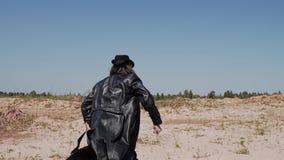 Een mens in een regenjas, een hoed en een mes in zijn handen die de woestijn doornemen stock footage
