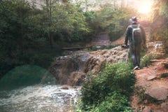 Een mens, een reiziger in een leerjasje en een een cowboyhoed en rugzak Grote volledig-stroomt waterval met vuil water, een reis, stock afbeeldingen