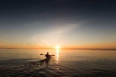 Een mens in een roeiboot die naar de zonsopgang gaan royalty-vrije stock afbeelding