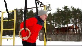 Een mens in een rood jasje die gymnastiek Stationaire Ringen in openlucht in de winter doen stock videobeelden