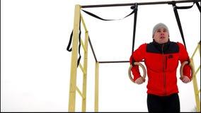 Een mens in een rood jasje die gymnastiek Stationaire Ringen in openlucht in de winter doen stock video