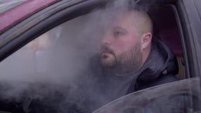 Een mens rookt vape in de auto stock video
