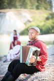 Een mens in Russische nationale kostuumtribune op de achtergrond van een verbazende landschap het spelen harmonika, het glimlache stock fotografie
