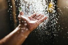Een mens ` s dient een nevel van water in het zonlicht tegen een donkere achtergrond in Water als symbool van zuiverheid en het l stock foto