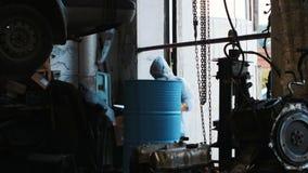 Een mens schildert een vat in een pakhuis Het meisje snijdt op het vat met een nevel van verf stock videobeelden