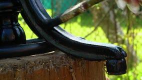Een mens schildert het krullende been van een stoel met zwarte verf stock footage