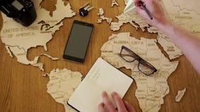Een mens schrijft in zijn notitieboekje het plan voor zijn reizen Duitsland, Spanje, Egypte, Turkije - en herschikt het document  stock video
