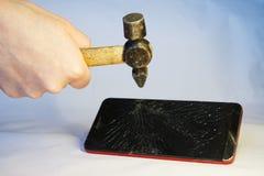 Een mens slaat een hamer op het scherm van een smartphone royalty-vrije stock foto's