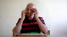 Een mens smeert zijn gezicht met een appel voor huidverjonging Masker van appelen voor het gezicht middelen om rimpels te verwijd stock footage