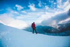 Een mens in sneeuwschoenen in de bergen stock foto