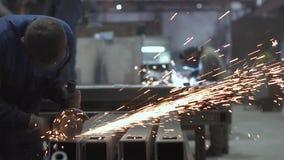 Een mens snijdt metaal met een cirkelzaag, worden de lassende werken uitgevoerd op de achtergrond Vonken van het werken met metaa stock videobeelden