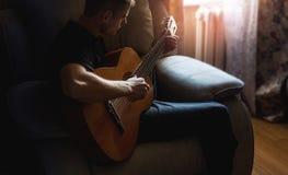 Een mens speelt een akoestische gitaar thuis in een ruimte, een hobby, een musicus stock foto's