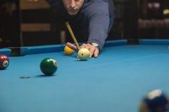Een mens speelt een biljart bij de club stock foto's