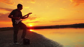 Een mens speelt de elektrische gitaarrots bij zonsondergang stock videobeelden