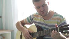 Een mens speelt de gitaar en zingt een lied stock videobeelden