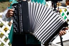 Een mens speelt de harmonika in het park van de de zomerstad Muzikale instrumenten en actieve levensstijl stock foto