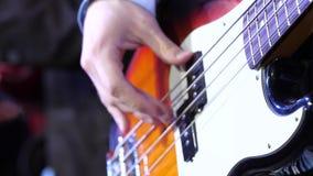 Een mens speelt gitaar op stadium Jonge mens het spelen op elektrisch gitaarclose-up De elektriciteit van het de handspel van kun stock videobeelden