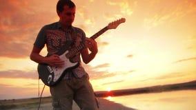 Een mens speelt het elektrische gitaar en rots springen stock video