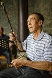 Een mens speelt het traditionele muzikale instrument dat Erhu of Nanhu en geluiden zoals een viool, China wordt genoemd Stock Foto