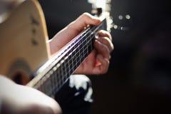 Een mens speelt een lied op een akoestische gitaar stock afbeeldingen