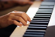 Een mens speelt een melodie op een toetsenbordinstrument royalty-vrije stock afbeelding