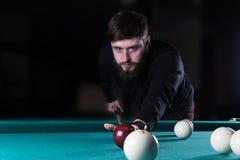 Een mens speelt een spel van pool Pool het noteren van de bal stock fotografie