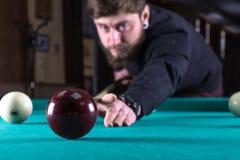 Een mens speelt een spel van pool Pool het noteren van de bal stock afbeeldingen