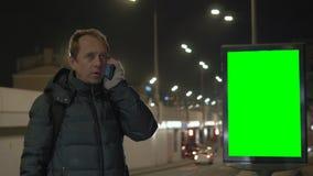 Een mens spreekt op de telefoon bij nacht in de stad Tegen de achtergrond is er een aanplakbord met het groen scherm stock video