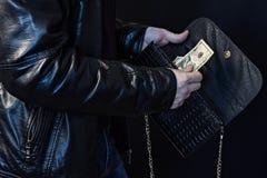 Een mens steelt geld van een vrouwelijke zak, zwarte achtergrond, close-up, Vrouwelijke zak stock foto's