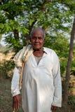 Een mens stelt voor een foto terwijl het hoeden van vee buiten Bhadarsa stock afbeelding