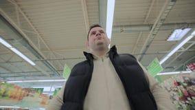Een mens in een supermarkt draagt een karretje, timelapse stock video