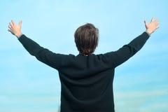 Een mens tegen de hemel gaat en geniet van het leven achteruit Een mens geniet van goed weer De mens hief omhoog zijn handen en l stock afbeeldingen