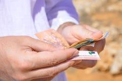 Een mens telt geld voor betaling op de weg Stock Foto