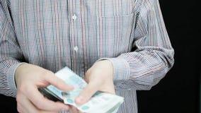 Een mens telt geld, vouwt het en zet het in zijn zak stock videobeelden