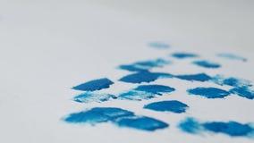 Een mens trekt blauwe verf op een wit blad van de sneeuw van het Nieuwjaar, close-up, nieuw jaar 2109, Kerstmis, de vakantie van  stock videobeelden