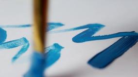 Een mens trekt een blauwe verf op een wit blad van een Kerstboom, close-up, nieuw jaar 2109, Kerstmis stock footage