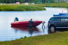 Een mens trekt een boot uit het meer Bootlancering De machine trekt de boot uit het water Visserij op de boot stock afbeelding