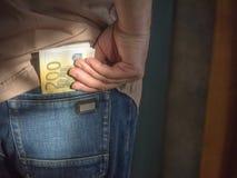 Een mens trekt een hand van zijn achterjeans in eigen zak steekt een pakje van contant geld in benaming van 200 euro Royalty-vrije Stock Fotografie