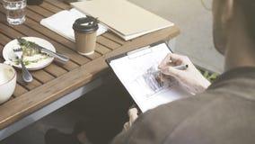 Een mens trekt in openlucht een schets bij koffie stock afbeelding