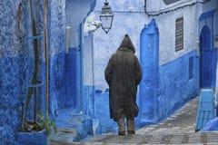 Een mens in typische Marokkaanse kleding, blauwe Medina van Chefchaouen royalty-vrije stock afbeeldingen