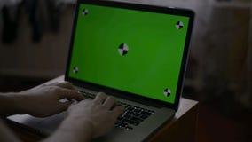 Een Mens typt op Laptop op Zijn Bureau Het groene scherm voor uw inhoud van het douanescherm stock video