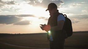 Een mens van de silhouet jonge toerist met een rugzak gebruikt een mobiele telefoon In de stralen van de het plaatsen zon Langzam stock video