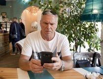 Een mens van leeftijdszitting in een koffie stock fotografie