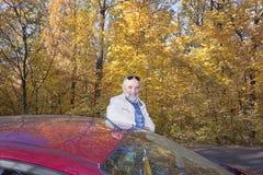 Een mens van rijpe die leeftijd rust op het dak van een auto op sid wordt geparkeerd stock foto's