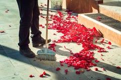 Een mens veegt toenam bloemblaadjes op de straat na de huwelijksceremonie stock foto's
