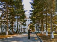 Een mens veegt een weg aan het sanatoriumgebouw met een bezem royalty-vrije stock foto's