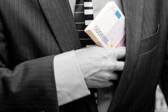 Een mens verbergt een bundel van geld in zijn zak royalty-vrije stock afbeelding