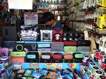 Een mens verkoopt een grote verscheidenheid van elektronika en gadgetstoebehoren in zijn opslag in Antipolo-Stad Stock Foto