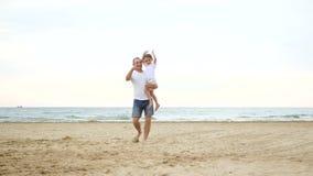 Een mens vervoert een kind op zijn schouder langs een zandig strand dichtbij de overzeese kust, in langzame motie stock footage