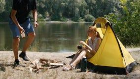 Een mens verzamelt brandhout voor een brand dichtbij de tent Het meisje zit in een tent en drinkt thee Wandeling, reis, groen toe stock footage